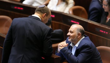 United Arab List's Mansour Abbas speaks with Prime Minister Naftali Bennett as the Knesset is sworn in, Sunday.