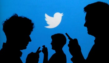 People holding mobile phones are silhouetted against a backdrop projected with the Twitter logo in this illustration picture taken in 2013.