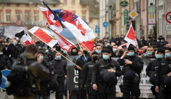 Supporters of the right-wing extremist NPD move through the city with a strong police presence in Greifswald, Germany, last month.