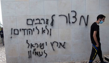 """A wall spray-painted with anti-Palestinian graffiti in Hebrew that read, """"a siege on the Arabs, not on the Jews, the land of Israel is for Israelis,"""" at a mosque in el-Bireh, near Ramallah in 2020."""