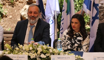 Shas chairman Arye Dery, seated next to Yamina Minister Ayelet Shaked, at the ceremony for the switching of interior ministers in Jerusalem, Monday.