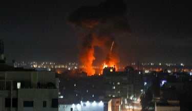 Explosions light-up the night sky above buildings in Gaza City as Israeli forces shell the Palestinian enclave, early on June 16, 2021