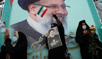 A supporter of Ebrahim Raisi displays his portrait during a celebratory rally for his presidential election victory in Tehran, Iran 2021.