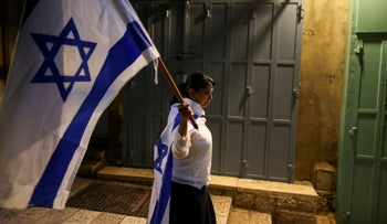 A woman carries an Israeli national flag as she walks in an alley in Jerusalem's Old City, June 2021.