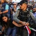 An Israeli policeman confiscates a Palestinian flag from a Palestinian woman as far-right Israelis participate in the Flag March at Damascus Gate, just outside Jerusalem's Old City last week