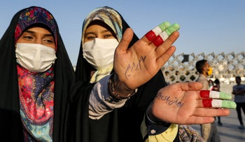 """Women flash their hands with their index and middle fingers painted with the colours of the Iranian flag, and inscribed on one hand text in Persian reading """"Rouhani bye-bye"""", during a rally celebrating the victory of Iran's newly-elected president Ebrahim Raisi in Imam Hussein square in the capital Tehran on June 19, 2021."""