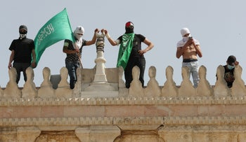 A Palestinian holds a Hamas flag as he stands next to others atop a walk of the al-Aqsa Mosque following clashes with Israeli police, in Jerusalem's Old City, last month