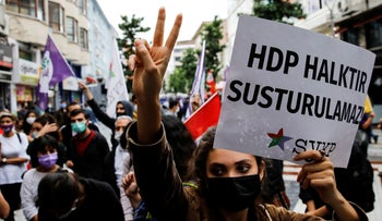 """A demonstrator holds a banner reads """"HDP is people, they can't be silenced"""" during a protest in solidarity with pro-Kurdish Peoples' Democratic Party (HDP), during a protest in Istanbul, Turkey , Friday."""