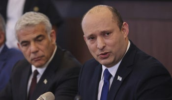 Prime Minister Naftali Bennett, right, and Foreign Minister Yair Lapid at the first cabinet meeting of the new Israeli government, in Jerusalem on Sunday.