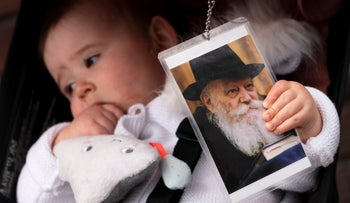 A baby girl clutches a photo of the late Rabbi Menachem Schneerson during a holiday celebration of Lag BaOmer in front of the Chabad Lubavitch World Headquarters earlier this year in New York