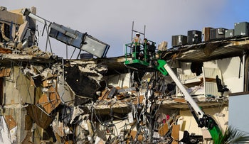 Rescue workers on a crane inspect the wreckage of the partially collapsed building in Surfside, north of Miami Beach, Friday.