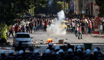 A fire burns between a formation of Palestinian police officers and demonstrators during a protest over the death of Nizar Banat, a critic of the Palestinian Authority, in Ramallah, Saturday.