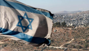 An Israeli flag flutters in Evyatar, a newly-built settler outpost overlooking the Palestinian village of Beita, south of Nablus in the occupied West Bank this month
