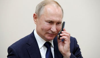 Russian President Vladimir Putin talks on the phone. Israeli justices refused to hear a case about the sale of phone hacking tech to Russia
