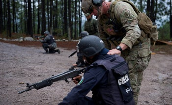 A U.S. soldier training a member of Honduras' elite Tigres unit, carrying an Israeli-made Galil automatic rifle, in 2014. Israel's Defense Ministry does not monitor how the weapons are used or by whom.