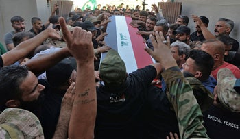 Mourners attend the funeral of a Hashed al-Shaabi paramilitary fighter following U.S. air strikes on the Syrian-Iraqi border, in Iraq. Monday.