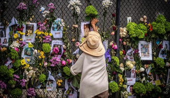 A woman adds flowers to a memorial featuring photos of some of those lost in the Surfside, Florida condo disaster.