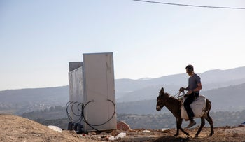 An Israeli settler rides a donkey in the recently established wildcat outpost of Evyatar, earlier this week
