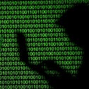 Silhouettes of laptop users are seen next to a screen projection of binary code in this picture illustration.