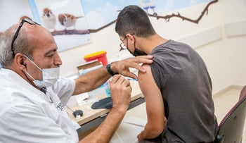 An adolescent receiving his COVID vaccination in Jerusalem, last month.