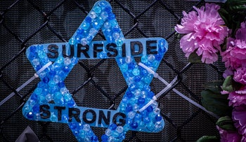 """A Star of David with the words """"SURFSIDE STRONG"""" placed on the monument that has images of some of the missing from the 12-story Champlain Towers South condo building in Florida, yesterday."""