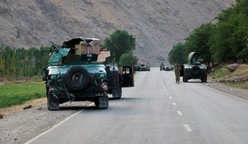 Afghan soldiers pause on a road at the front line of fighting between Taliban and Security forces,  near the city of Badakhshan, northern Afghanistan, yesterday.