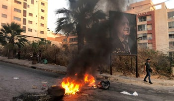 A man walks past a fire set during a protest against mounting economic hardships in Beirut, last month.