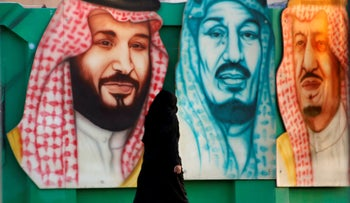A woman walks in front of a banner showing (from R) Saudi King Salman, Crown Prince Mohammed bin Salmanand Saudi Arabia's founder late King Abdul Aziz Al Saud. Dammam, last month