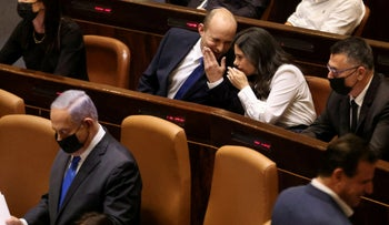 Prime Minister Naftali Bennett and Interior Minister Ayelet Shaked, speak to each other as Israeli Prime Minister Benjamin Netanyahu sits nearby the swearing-in of the new government, in June.