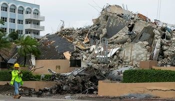 A worker makes her way past the rubble and debris of the Champlain Towers South condo