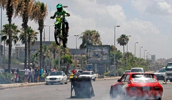 """A Lebanese motorcycle rider jumps over a drifting car during a show entitled """"Calm Down"""", in light of the severe economic crisis that Lebanon is witnessing in the southern city of Sidon (Saida), on July 4, 2021."""