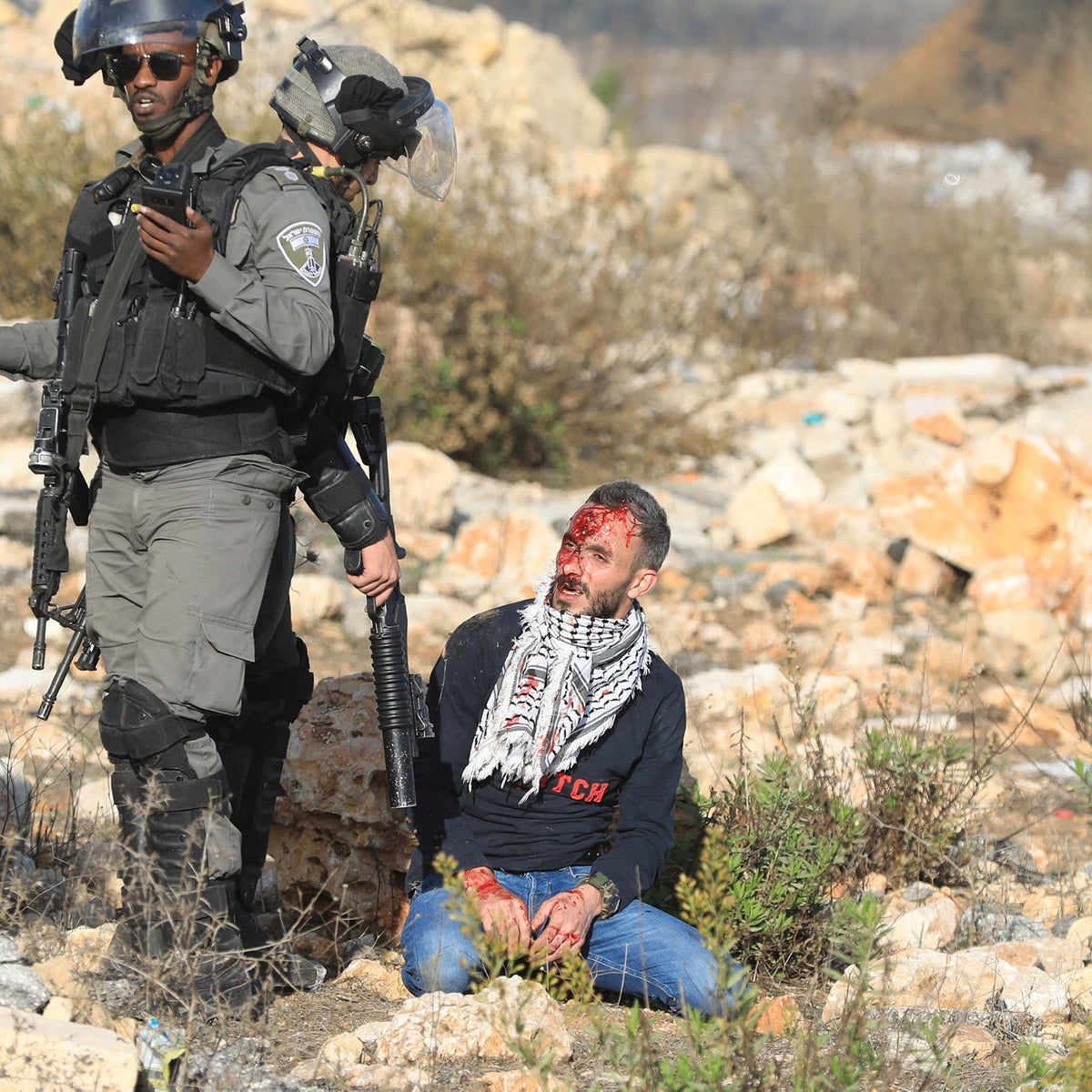 Israeli forces surround a wounded activist, Fadi Washaha, during a protest against Israeli army attacks on Gaza, at the Beit El checkpoint in Ramallah, in November 2019.