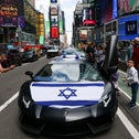 People take pictures of decorated cars in a small car parade to celebrate Israel's Independence Day, which marks the 73rd anniversary of the creation of the state, in Times Square in New York City, U.S., April 18, 2021. REUTERS/Caitlin Ochs
