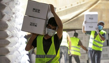 Workers carry boxes of humanitarian aid near Bab al-Hawa crossing at the Syrian-Turkish border, in Idlib governorate, Syria