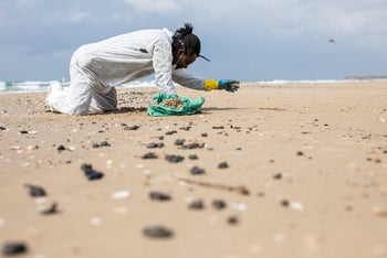 Cleaning up tar at a beach at Beit Yanai, central Israel, after an oil spill in March.