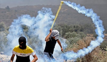 A Palestinian protester hurls back a tear gas canister towards Israeli forces during clashes in Beita, opposite the newly-established Israeli wildcat settler outpost of Eviatar, last Friday.