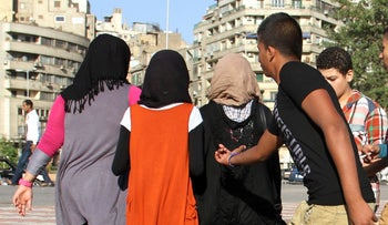 An Egyptian youth reaches for young girls in Cairo, 2012.