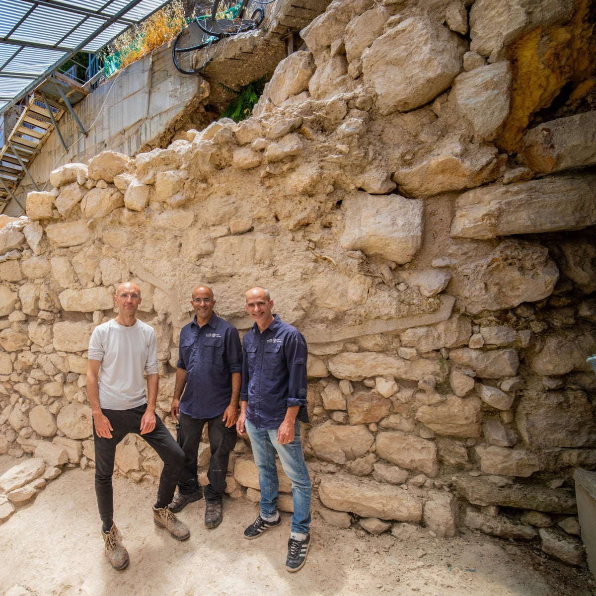 Excavation directors Dr. Joe Uziel, Ortal Kalaf, and Dr. Filip Vukosavovic standing by the newly discovered section of Jerusalem's ancient defensive wall.